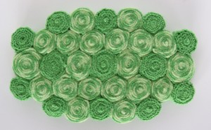 """A 100% wool sweater, felted, cut, and sewn by hand has been transformed and recycled into this 5"""" x 8"""" trivet."""