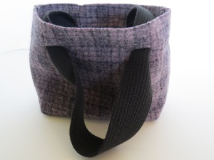 A mini skirt turned mini bag. Lined with black linen, with the button and buttonholes remaining inside along the top edge.