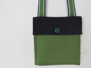 A pocket bag of merino wool, green and blue. the strap is a J. Crew ribbon belt.