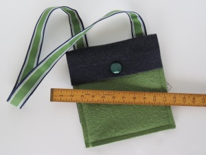 And the strap? A J. Crew ribbon belt with stiff interfacing, and very heavy d-rings attached at the back of the bag to hang your id or keys.  (There is no J.Crew.)