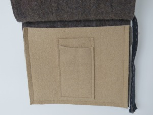 Front cable knit flap lifts to reveal one large pocket and two small. iPad and iPhone, I'd say.