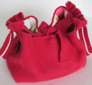 A nice roomy bag emerged from this cranberry red ribbed cashmere. It had frills on the edges of the sleeves, which I incorporated. The lining is a large print of tulips, with a yellow slip pocket.